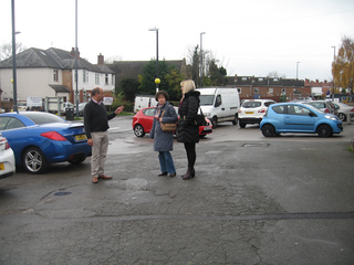 Cllrs Joe Naitta and Ruth Skelton with Danielle Lind discuss rat running through the car park in front of the shops at the Lane End