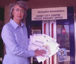 Cllr Lucy Care outside Derby's Police Enquiry Office with some of the returned petitions