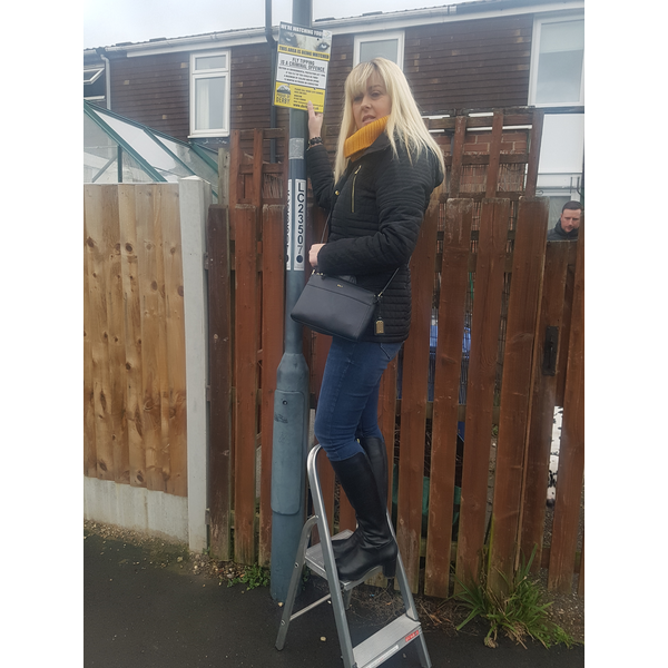 Danielle Lind puts up one of the No Fly Tipping signs
